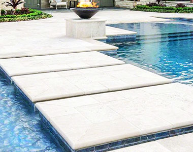 Travertine pool coping and white stone pavers