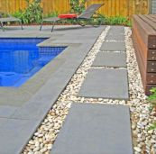 Outdoor Bluestone Pavers laid amoungst pebbles for a classic backyard look