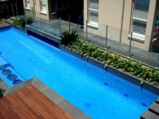 Bullnosed Bluestone Pool Coping contrasting with timber decking