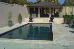 Matching sandstone pool coping, pool pavers and retaining wall