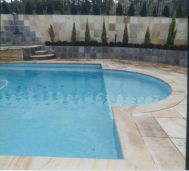 Outdoor sandstone pool paving and matching bullnose pool coping pavers