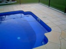 Sandblasted Sandstone Paving and bullnosed pool coping pavers have been put around this swimming pool