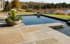 Natural split Sandstone Paving and pool coping pavers have been laid around this swimming pool